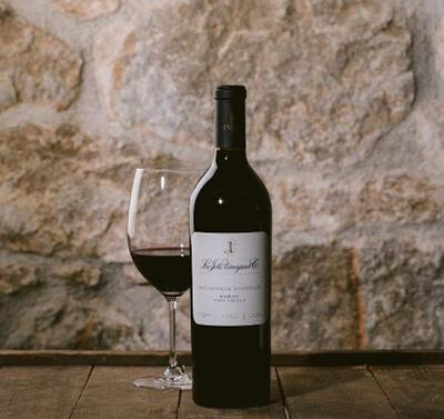Wine bottle against a stonebackdrop with a wine glass off to the side with red wine