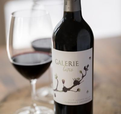 Red wine bottle with a glass of wine in the background on the left