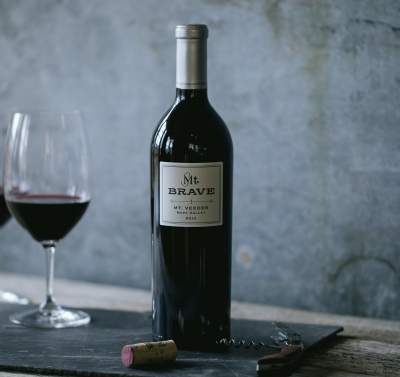 Bottle of wine with a slate gray background and two wine glasses on the left