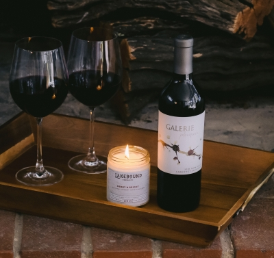 Single bottle of red wine on a tray with a candle