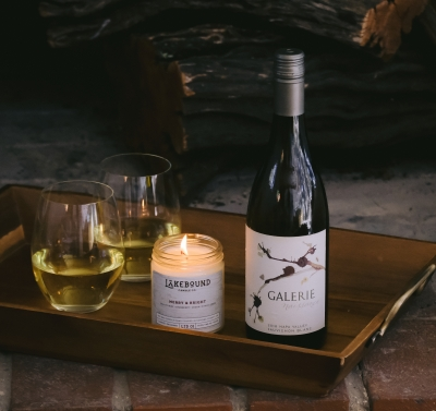 Single bottle of white wine on a tray with a candle