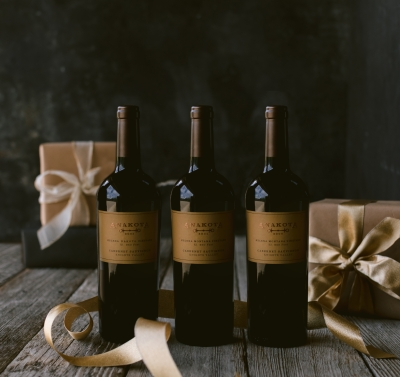 Three bottles of wine against a dark background with gifts behind the wines