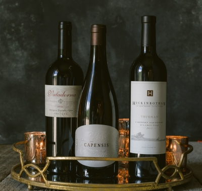 Three bottles of wine against a dark background on a serving tray