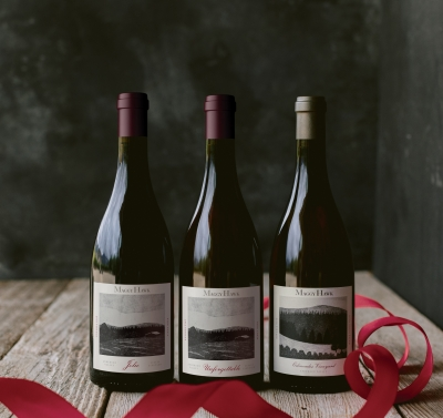 Three bottles of wine against a dark background