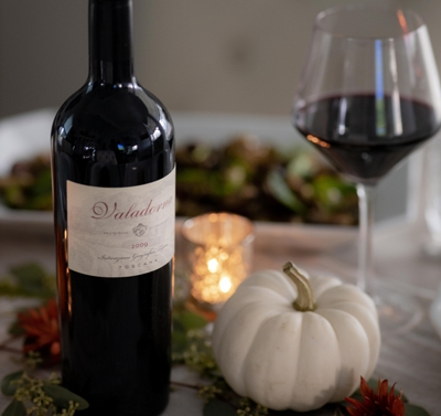 Bottle of wine, glass, and small white pumpkin on a table with holiday setting in the background.
